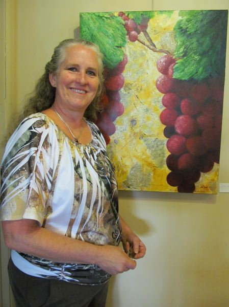 by: PHOTO BY ELLEN SPITALERI - Karen Grondin, owner of the gallery at Singer Hill Cafe is drawn to this painting by Jodi Dann, who incorporates maps of Oregon wine country into her work.