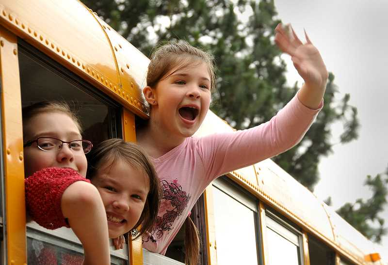 by: VERN UYETAKE - Anna Reese, right, waves goodbye from the school bus to friends and staff at Cedaroak Park Primary School on the last day of school on June 14.