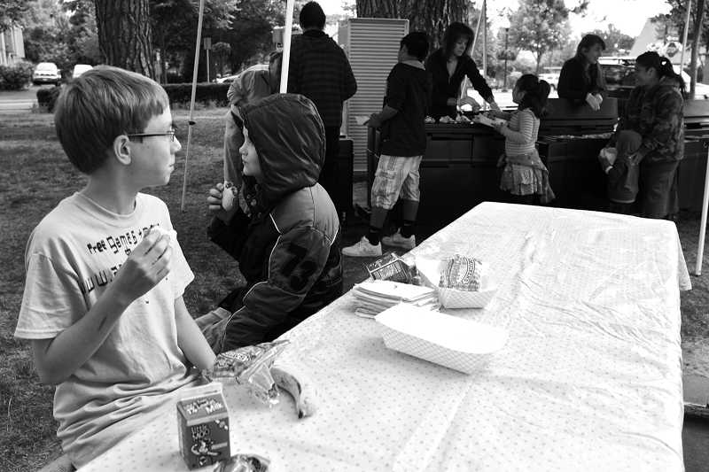 by: TIMES PHOTO: JAIME VALDEZ - Aaron Esau, 11, and his brother Timmy, 10, enjoy lunch at Beaverton City Park put on by the Summer Food Program.