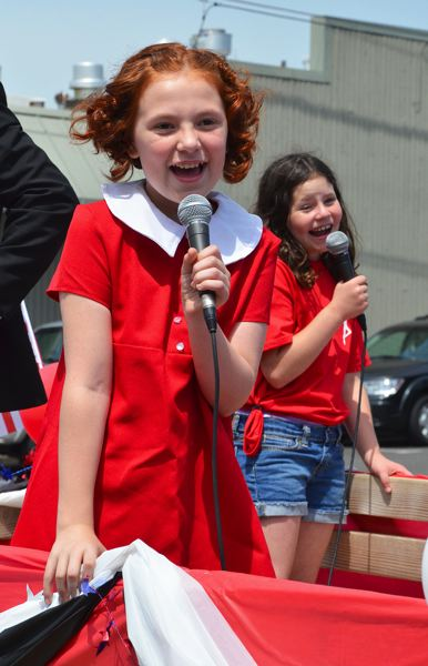 by: JOHN BREWINGTON - 'Annie' sang a few songs for the crowd at the St. Helens Kiwanis Club Community Parade last Saturday. Annabelle Robitz is starring as Annie in the upcoming musical at the Scappoose High Auditorium. Johanna Bennett (behind Robitz) plays Molly in the Shoestring Players production which will run July 11-13, and 18-20. Much of the cast for Annie was on hand for the parade.