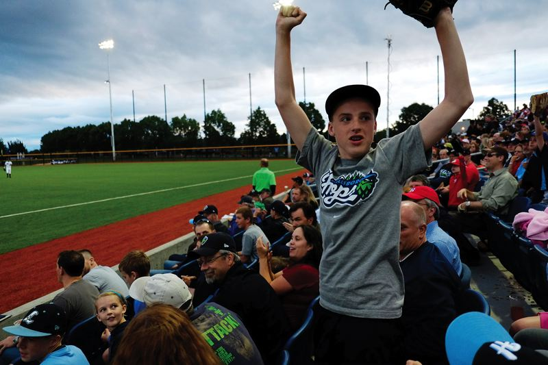 by: HILLSBORO TRIBUNE PHOTO: CHASE ALLGOOD - A young Hillsboro Hops fan celebrates after catching a baseball during a promotional giveaway at the new minor league baseball team's first home game on Monday evening.