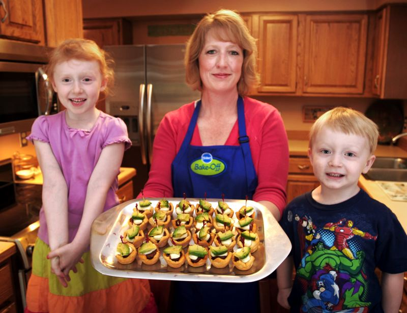 by: OUTLOOK PHOTO: JIM CLARK - Carolyn Westerback, here with her children Genevieve, left, and Henry, shows off her Chipotle Meatball Appetizers, one of 60 recipes people can vote on online. She hopes to win the chance to go to the finals in Las Vegas where 100 recipes will vie for the $1 million prize.