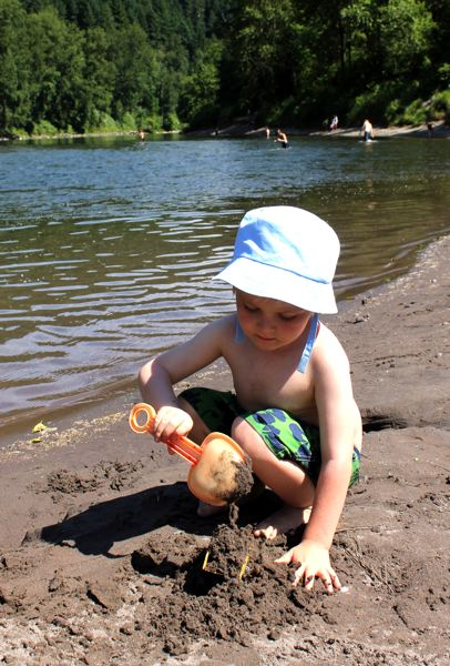 by: OUTLOOK PHOTO: CARI HACHMANN - August Wells, 3, is building the beginnings of a sand castle on the bank of the Sandy River.