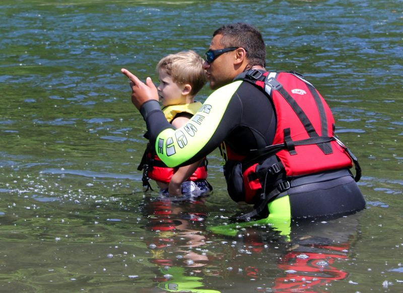 by: OUTLOOK PHOTO: CARI HACHMANN - River lifeguard Shawn Houston shows Cameron Chaussee, 3, which direction the river flows.