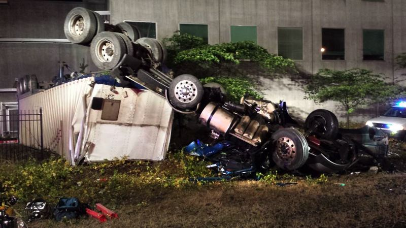 by: CONTRIBUTED PHOTO - A semi-truck pulling a 53 foot trailer crashes 49 feet below a freeway ramp at the Interstate 84 and Interstate 5 interchange.