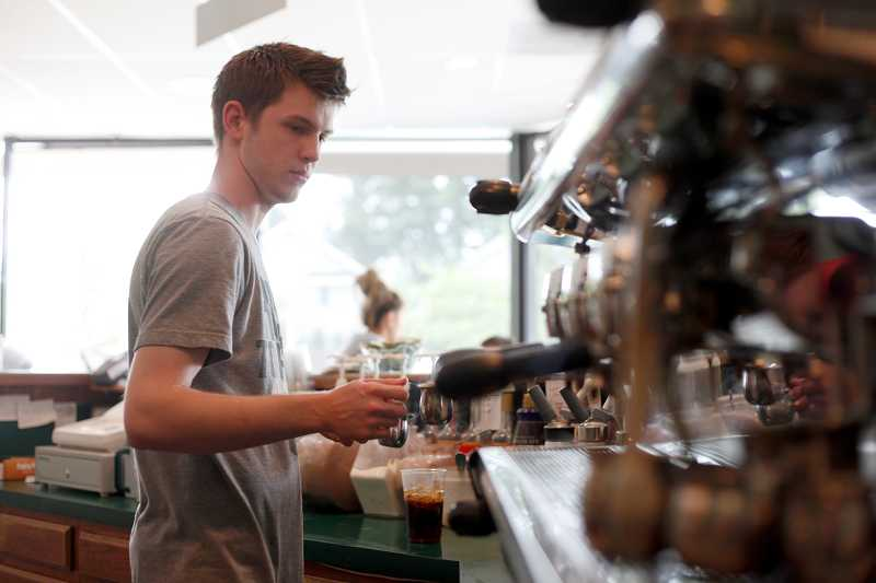 by: JONATHAN HOUSE - Ian Walters, 20, makes iced coffee at Primo Espresso on Southwest Hall Boulevard. Walters bought the store at the age of 19 after working there for four years.