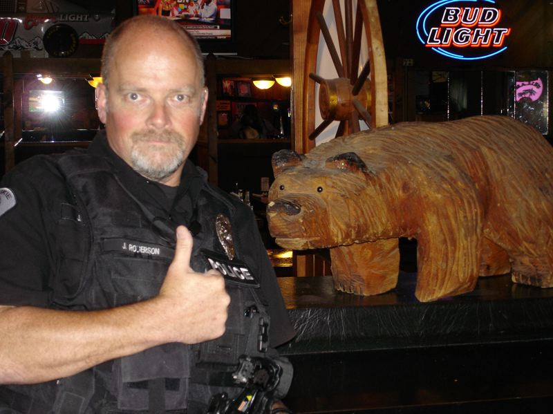 PHOTO COURTESY: MILWAUKIE POLICE DEPARTMENT - MPD Officer Jeff Rogerson returns a stolen bear statue to the Wichita Pub on Friday.