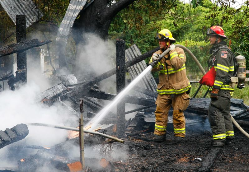 by: HILLSBORO FIRE AND RESCUE - Hillsboro firefighter s mop up hot spots at a Sunday morning barn fire. The barn was on a north Hillsboro property leased by former country music star Tommy Overstreet.