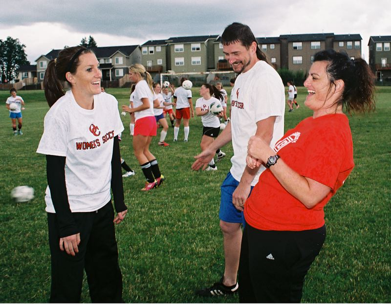 by: JOHN DENNY - New head coaches Alissa Russell (left) and Becket Wright (right) and assistant coach Marshall Brewer bring a newfound enthusiasm to Oregon City High School girls soccer.