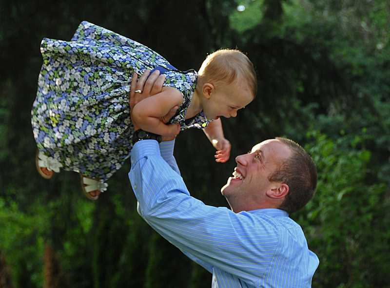 by: VERN UYETAKE - Josh Henle takes his baby daughter Lauren airborne during a playful session at their Lake Oswego home. Having his own young daughter made the Donald Cockrell trial especially impactful on Henle.