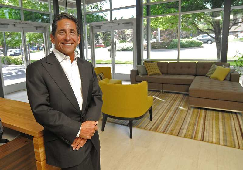 by: VERN UYETAKE - Mike Hasson, owner and founder of The Hasson Company Realtors, stands in the living room of the newly renovated Lake Oswego office.