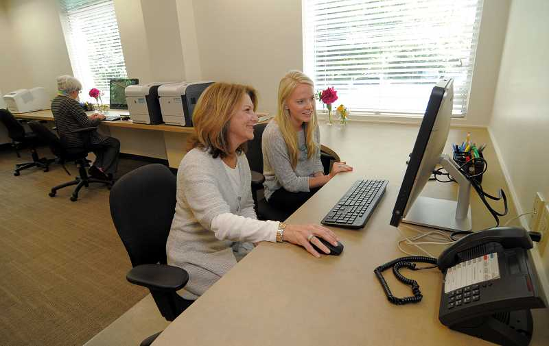 by: VERN UYETAKE - Agent Emily Iverson gets assistance from agent services team member Caitlin McCloskey, at right.