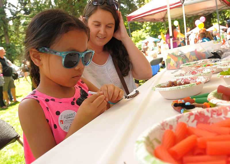 by: VERN UYETAKE - Melia Kramer, 7, makes a bracelet at Gymborees Kids Day activity at the festival in George Rogers Park.