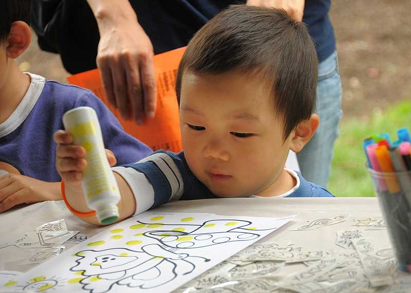 by: VERN UYETAKE - Dihan Feng, 3, of Lake Oswego, works on an art project at Frog Pond Toy's Kids Day activity.