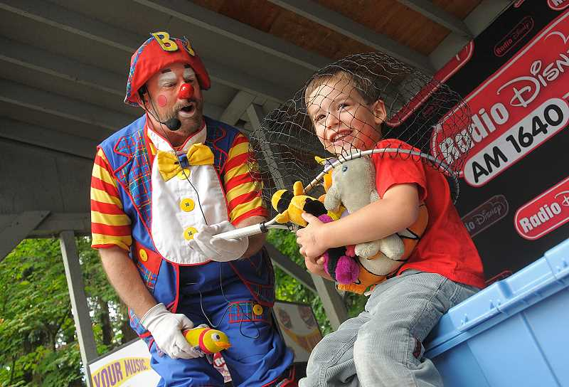 by: VERN UYETAKE - Roman Yruretagoyena, 4, has fun clowning around with BJ the Clown during Friday's Kids Day activities.