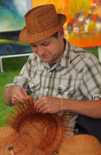 by: VERN UYETAKE - Jordan Mercier from one of the festival's sponsors,  the Confederated Tribes of Grand Ronde, gives a basket weaving demonstration.