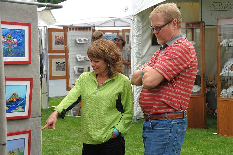 by: VERN UYETAKE - Dan Ashland and Dana Freeman admire the art work of Larry McKee at the Art in the Park.