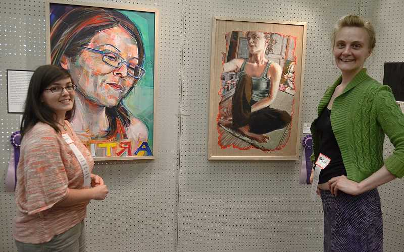 by: VERN UYETAKE - Becca  Bernstein, left, and Gwenn Seemel stand next to portraits each did of the other at the Arts Chronicles exhibit.