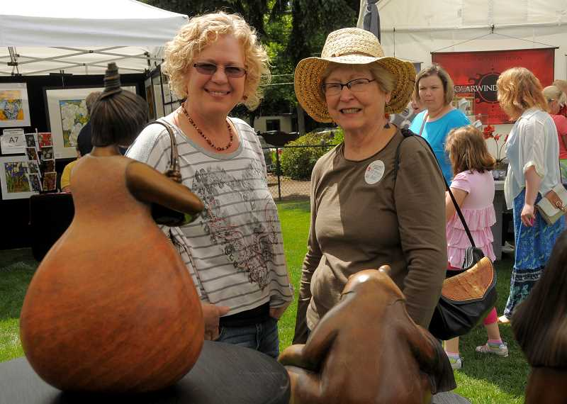 by: VERN UYETAKE - Liane Lawrence, left, and Darlene Thompson find a bronze sculpture by Ann Fleming that they really like at the Art in the Park Crafts Fair.
