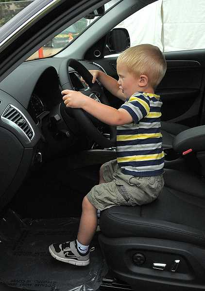 by: VERN UYETAKE - Baylor Boe, age 2, does some pretend driving in an Audi displayed by festival sponsor Audi of Wilsonville.