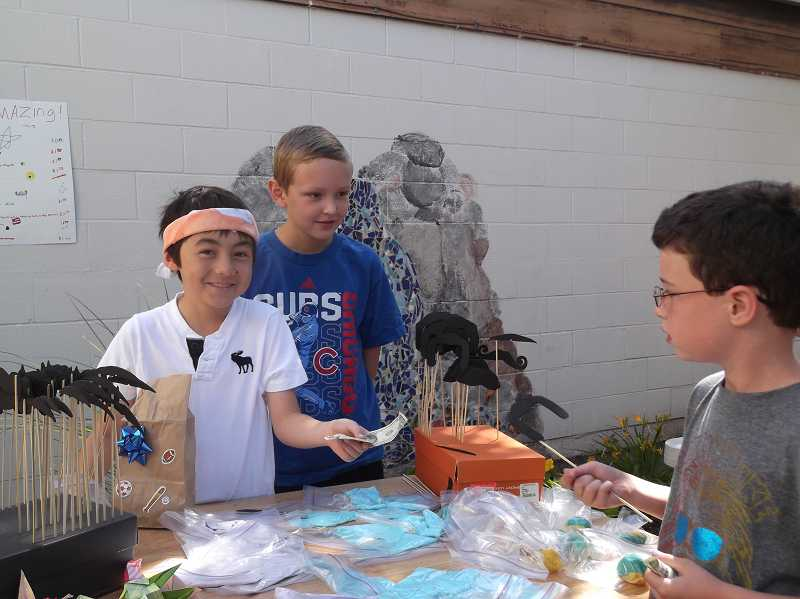 by: KATE HOOTS - Fourth-graders Ty Park, left, and Jonah Adams offered multiple items at their booth, including handheld moustaches like the one purchased by Sam Schecter.