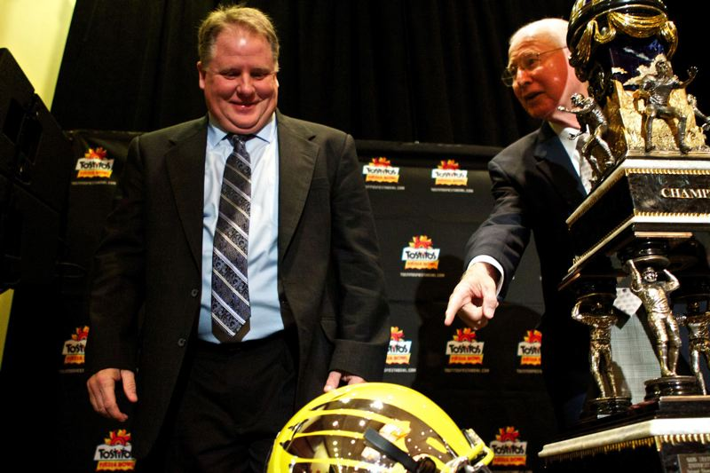 by: TRIBUNE FILE PHOTO: JAIME VALDEZ - Former Oregon Ducks coach Chip Kelly, admiring the Fiesta Bowl trophy before the 2013 game against Kansas State, admitted failed to monitor the UO program to NCAA regulations, but isn't likely to suffer from the penalties announced Wednesday.