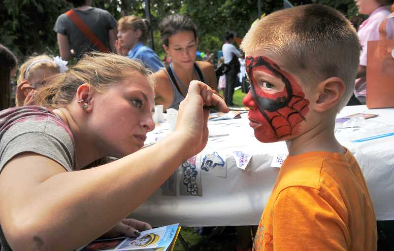 by: REVIEW PHOTOS: VERN UYETAKE - Giants fan Mattew Edelen admires the necklace he made at the Oregon Preschool Kids Day activity on Friday at George Rogers Park.
