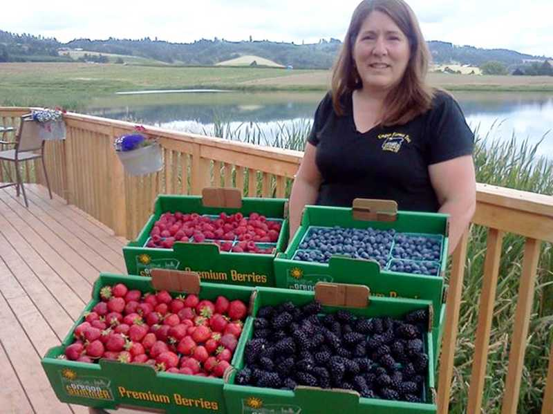 by: COURTESY PHOTO - Kathy Unger shows off fresh strawberries and blueberries, now in season and available at Unger Farms booth at the Forest Grove Farmers Market.