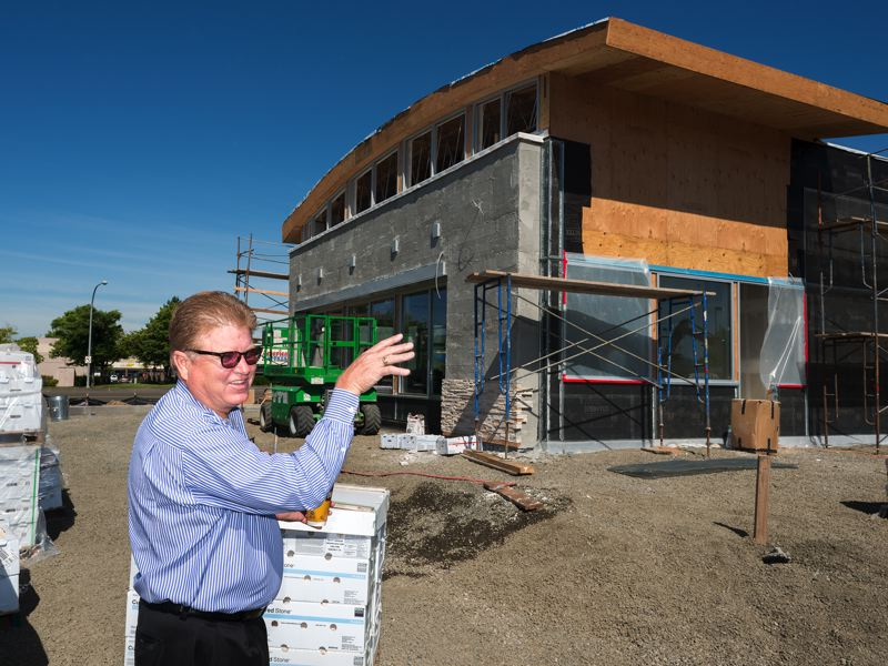 by: TRIBUNE PHOTO: CHASE ALLGOOD - McDonalds owner Don Armstrong points out where artistic sculptures and attractive landscaping will spruce up the appeal of his renovated restaurant on 185th Avenue.
