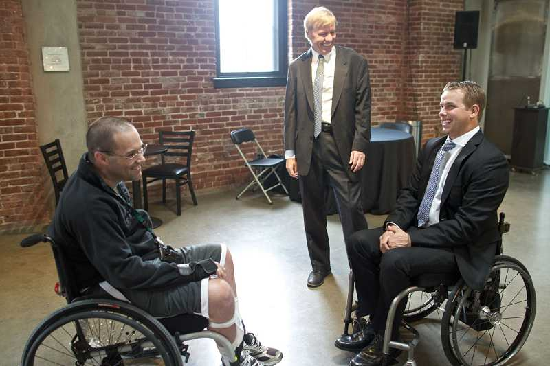 by: TIMES PHOTO: JAIME VALDEZ - Reeve Foundation CEO Peter Wilderotter watches as David Pierson, 35, of Oak Hills and Rob Summers of Beaverton, introduce each other before a reception hosted by the Christopher and Dana Reeve Foundation at Portland Center Stage Theater at the Armory.