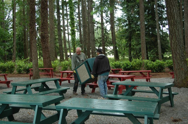 by: ESTACADA NEWS PHOTO: ISABEL GAUTSCHI - Don Olson and Kevin Harding make final arrangements in the beer gardens configuration before its opening June 22.