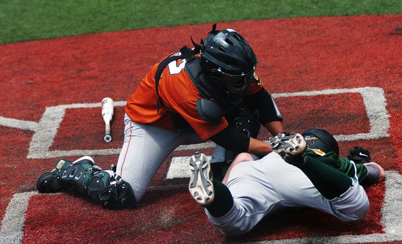 by: DAN BROOD - OUT AT HOME -- Tigard Longhorns catcher Bradley Imai (left) tags out West Linn's Braden Vogt at home plate during the second inning of Friday's game at the 2013 Grenade Gloves Classic held at Lake Oswego High School.