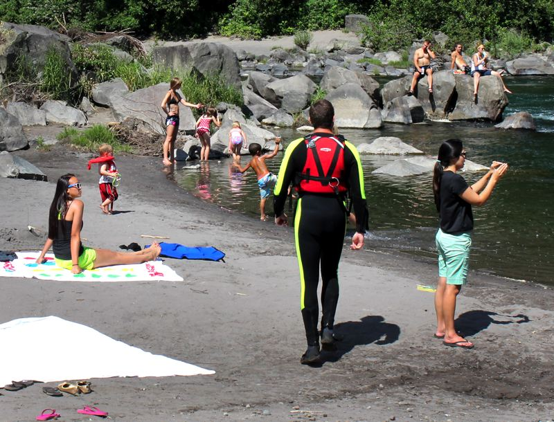 by: OUTLOOK PHOTO: CARI HACHMANN - River lifeguard Shawn Houston keeps an eye out for trouble along the Sandy River at Troutdale. With hot weather in the forecast, crowds are expected to increase along local waterways as people seek relief from the heat.