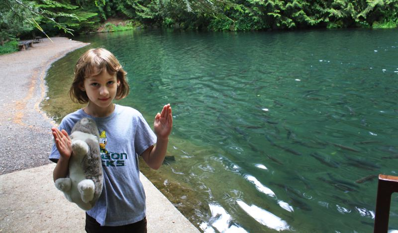 by: POST PHOTO: NEIL ZAWICKI - Gwen Hawkins, 8, illustrates the size of the fish she caught at Rainbow Trout Farm, located between Sandy and Welches off Highway 26. If you look closely enough, you can see the trout swimmming in the pond.