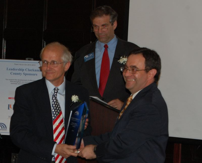 by: PHOTO BY: RAYMOND RENDLEMAN - Chip Sammons of Holistic Pet Center received the Irwin Adams Lifetime Achievement Award from Chamber CEO David Kelly, with returning Chamber Chairman Rob Wheeler at the microphone.