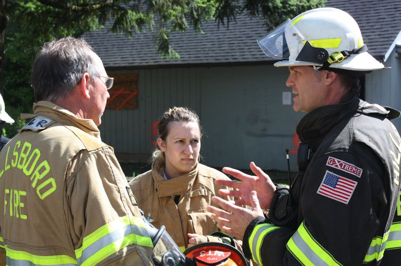by: HILLSBORO TRIBUNE PHOTO: DOUG BURKHARDT - The Hillsboro Fire Departments Nathan Leek (right) gives a final briefing to council members Megan Braze and Steve Callaway just before the trio entered a burning building on Saturday to get an unique, closeup look at the departments operations.