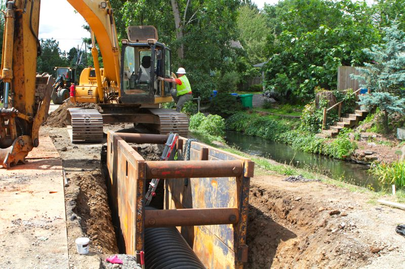by: DAVID F. ASHTON - In the ditch is a pipe that will temporarily divert Crystal Springs Creek, seen in the background, while workers construct a new, larger, fish-friendly culvert.
