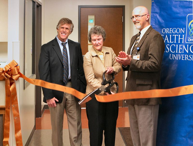 by: DAVID F. ASHTON - Cascadia Behavioral Healthcare CEO Derald Walker and OHSU Family Medicine Executive Director Erwin Teuber stand by - as Division-Clinton Business Association President Jean Baker cuts a ceremonial ribbon, signaling the opening of the joint venture: The Cascadia Plaza walk-in physical and mental health care clinic.