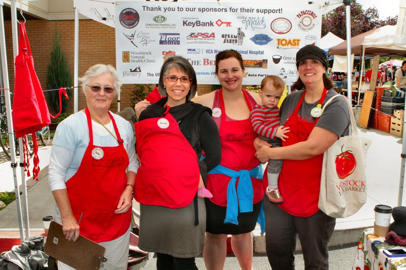 by: DAVID F. ASHTON - Woodstock Farmers Market volunteers Sandra Shaw, Amanda Owings, and Cicely Waters, take a break for a moment with Market Manager Emily Murnen - who is holding Owen.