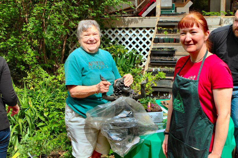 by: DAVID F. ASHTON - Neighbor Shirley Reynolds is ready to purchases plants from the plant sale organizer, Lisa Gunion-Rinker.