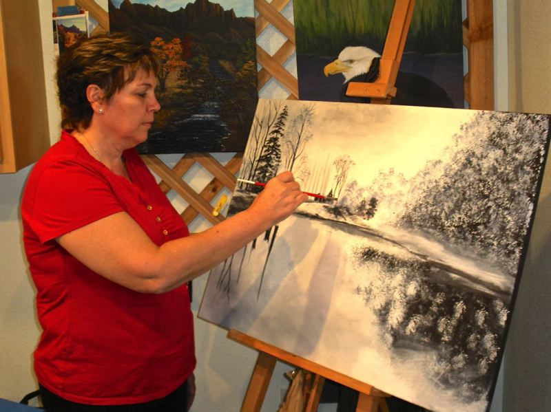 by: POST PHOTO: JIM HART - Sherrill Pratt, who lives a few miles southwest of Sandy, works on a black and white painting which shows that her repertoire goes beyond the usual. The spectrum of her work — paintings, photos, giclee prints and greeting cards — will be on display with the other 150 artists in the Sandy Mountain Festival, July 13-14.