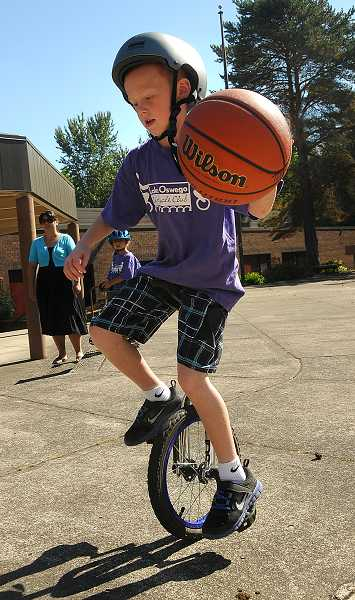 by: REVIEW PHOTO: VERN UYETAKE - Calvin Gregory, 7, dribbles the basketball while riding his unicycle.