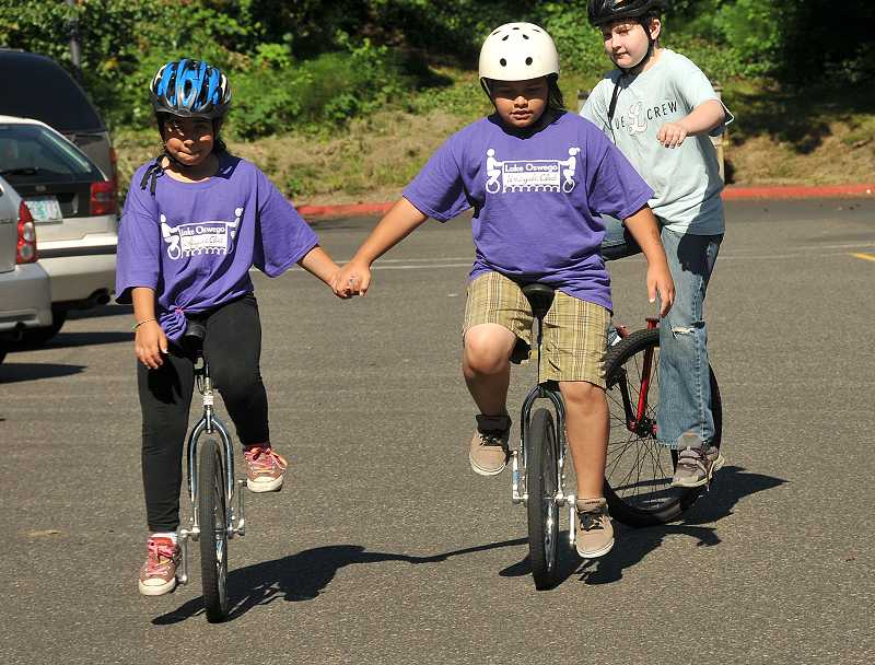 by: REVIEW PHOTO: VERN UYETAKE - Nisa Rivera, 9, on left, and her sister Dea Rivera, 11, ride together hand in hand.