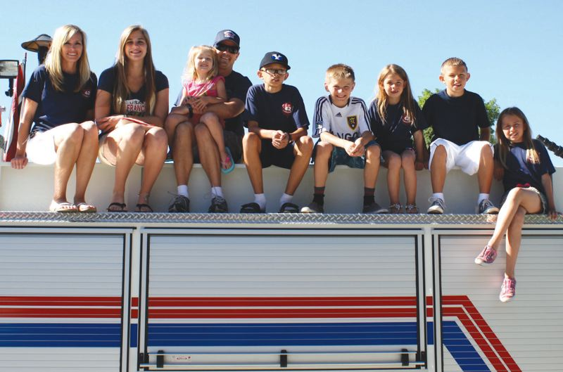 by: CONTRIBUTED PHOTO - Reynolds High graduate Brodie Berg went from a state champion golfer to a fire fighter in Salt Lake City. Here he (in sunglasses) is seen atop of fire engine with his family that includes wife Nicole and seven children.