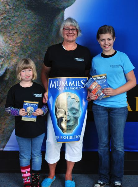 by: OREGON MUSEUM OF SCIENCE AND INDUSTRY - Twelve-year-old Ivy Gaelrun, right, was recognized as the millionth overall visitor to the Mummies of the World exhibit on Saturday, June 29, while at the Oregon Museum of Science and Industry with her grandmother Sue Maggi, center, and 7-year-old sister Lila Gaelrun, left.