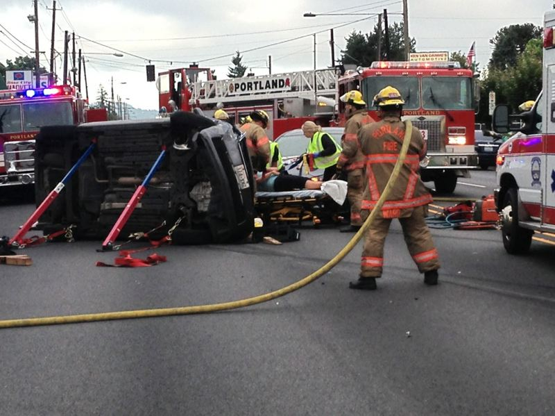 by: PORTLAND FIRE & RESCUE - Firefighters cut the roof off a vehicle to rescue an injured woman Monday morning.