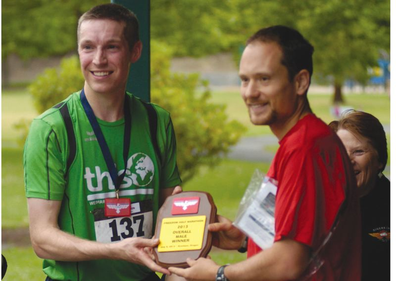 by: GRESHAM OUTLOOK: DAVID BALL - Barlow High graduate Scott Overby accepts an award from race founder Steve Walters after winning the half-marathon.