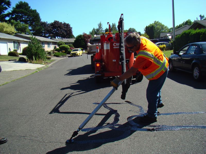 by: PHOTO COURTESY: CITY OF MILWAUKIE - Jim Bunting of the City of Milwaukie's Streets Department works in various neighborhoods this month to seal off cracks.