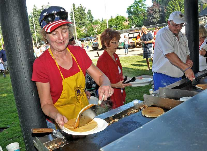 by: STAFF PHOTOS: VERN UYETAKE - Sandi Swinford was one of the many cooks flipping pancakes at the Lions Club's annual pancake breakfast on the Fourth of July.