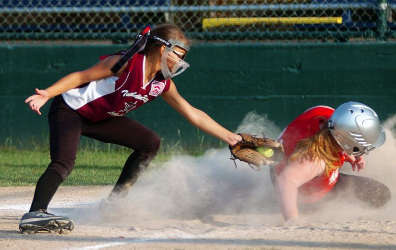 by: DAN BROOD - PLAY AT THE PLATE -- Tualatin City's Sasha Zuckerman (left) tries to tag out Murrayhill's Lauren Powell in Monday's district tourney game.